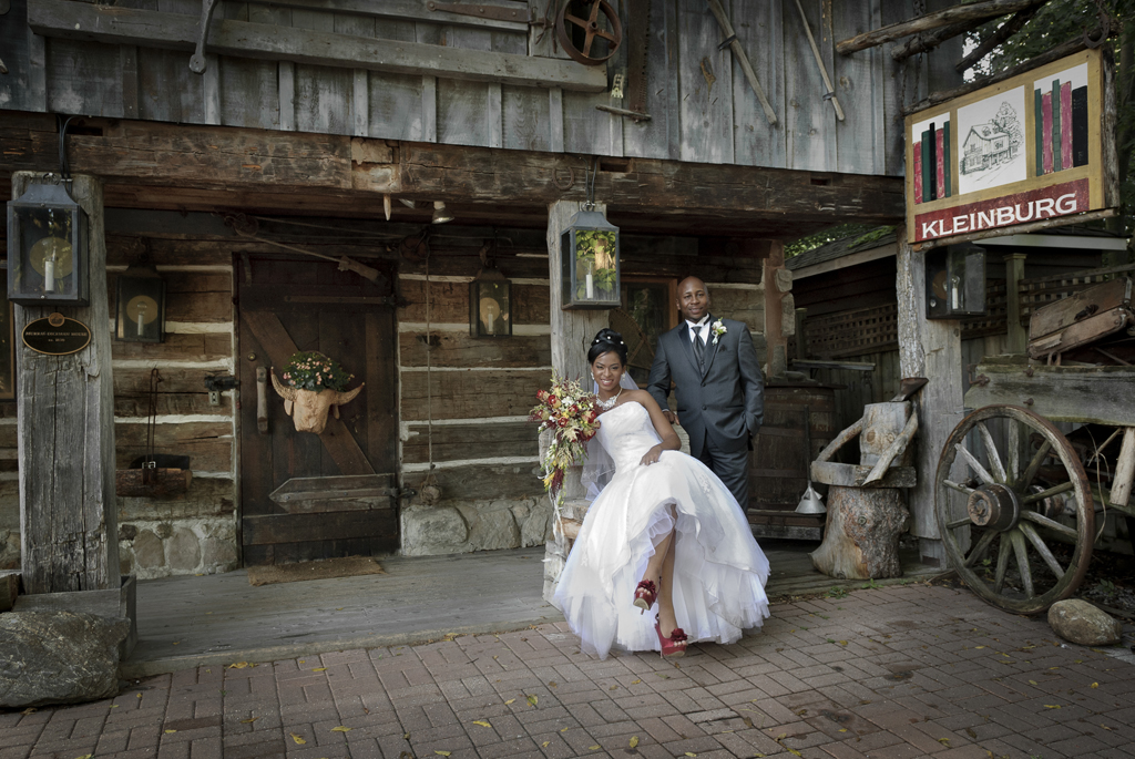 couple in front of an old log house in Kleinburg